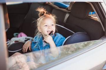 Little girl at the back seat of her Mom's car