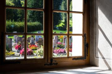 Graveyard through the church window in Blumenstein Switzerland