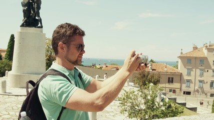 Young handsome bearded man making outdoor photos with his compact camera