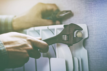 service man hands with wrench near radiator