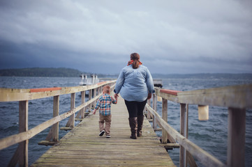 Mother and Son Walking Along Dock at the Pacific Ocean in Washington