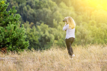 young girl takes pictures of beautiful nature toned