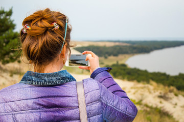 young girl takes pictures of beautiful nature