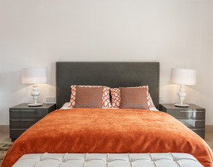 Modern bedroom has a bedroom with a bed and decorative pillows.