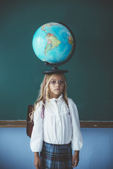 Pupil girl posing with globe