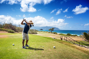 Golfer with straw hat teeing off with driver from ocean side par 4 hole