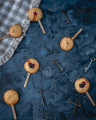 mini pies with berry filling on wooden sticks among flowers, old keys, textile on blue background, top view