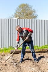 Farmer with rakes in the suburban area