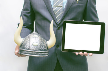 Stock broker. Bull speculation concept. Business man holding a bull hat with horns in hand and tablet computer with blank screen in another hand. Financial product presentation.