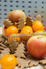 Apple, mandarins, christmas cookies in the shopping cart on the grey background