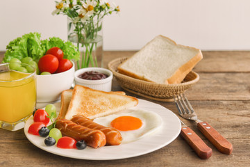 Homemade breakfast with sunny side up fried egg toast sausage fruits vegetable strawberry jam and orange juice in side view with copy space.Delicious homemade american breakfast concept for background