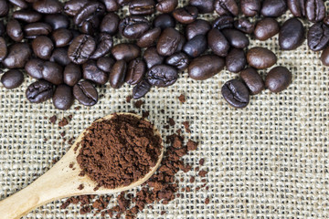 Coffee grind in wooden spoon on sackcloth with coffee beans background. Copy space.