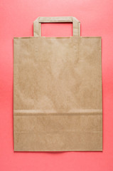 A paper bag over pink background. Top view and flat lay. Copy space for design