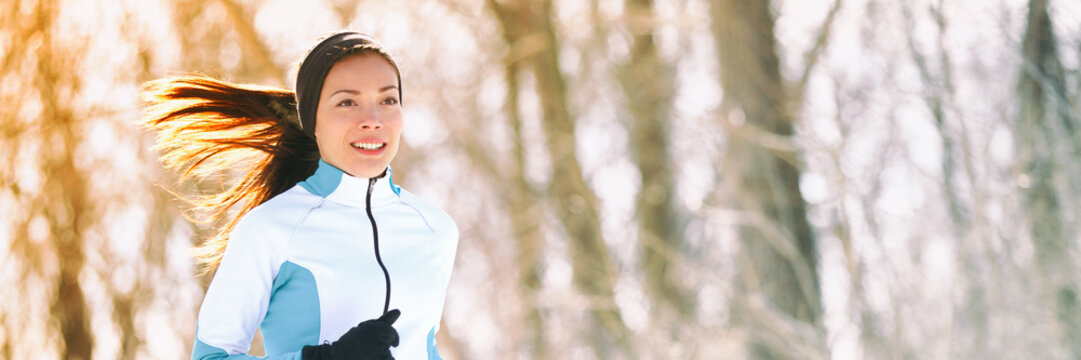 Winter run exercise woman running in park banner. Fit runner athlete panorama training in forest cold weather