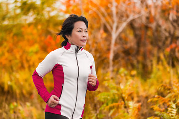 Active woman running and jogging. Middle aged Asian mature female jogger outdoor living healthy lifestyle in beautiful autumn city park in colorful fall foliage. Asian Chinese lady in her fifties.