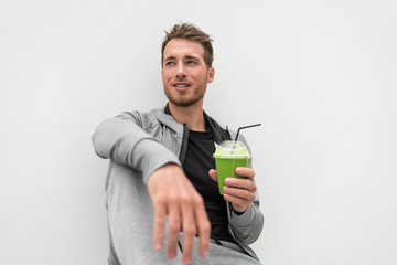Healthy man drinking green smoothie spinach juice at home relaxing. Young adult eating detox diet, active lifestyle.