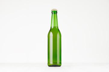 Green longneck beer bottle 500ml, mock up. Template for advertising, design, branding identity on white wood table.