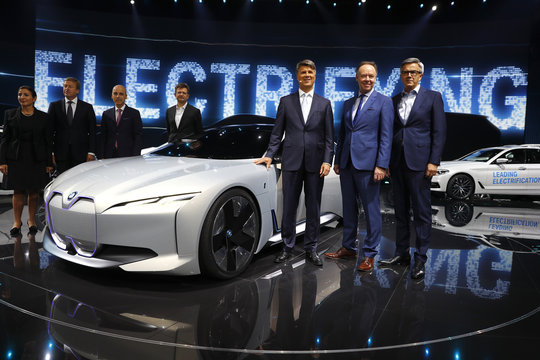 BMW CEO Krueger and board members Robertson and Schwarzenbauer pose next to the new BMW i Vision Dynamics during the Frankfurt Motor Show (IAA) in Frankfurt