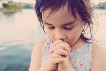 little multiethnic girl praying, kid, child pray concept,shallow DOF