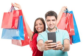 Girlfriend carrying shopping bags and boyfriend taking selfie