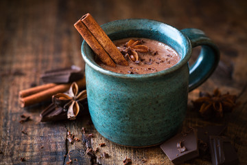 Hot chocolate with a cinnamon stick, anise star and grated chocolate topping in festive Christmas setting on dark rustic wooden background