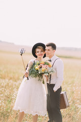 The view of the vintage dressed newlyweds are taking selfie using the selfiestick at the background of the sunny field.