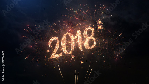 2018 happy new year greeting text with particles and sparks on black night sky with colored