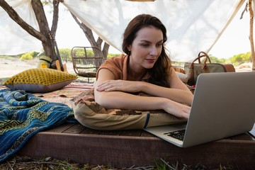 Woman using laptop in tent