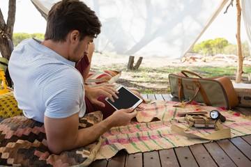 Man using digital tablet in tent
