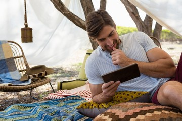 Man using tablet while resting in tent