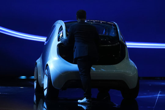 Man pushes back from the stage the new Smart concept autonomous car Vision EQ fortwo model during the Frankfurt Motor Show (IAA) in Frankfurt,