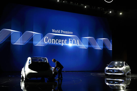 People try to push back from the stage the new Smart concept autonomous car Vision EQ fortwo model as the new Mercedes Concept EQA is presented during the Frankfurt Motor Show (IAA) in Frankfurt