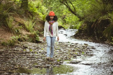 Full length of hiker walking by stream at forest
