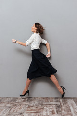 Vertical image of woman in business clothes running in studio