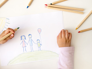 Kid drawing a happy family on white paper