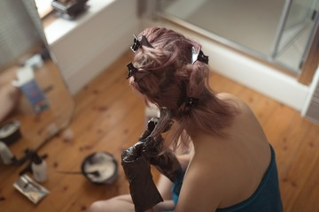High angle view of woman applying dye on hair