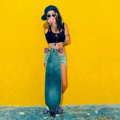Cool Frick Teenager girl on a yellow wall background with a skateboard
