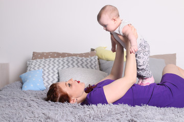 Young mother plays with her little baby on bed with pillows in bedroom