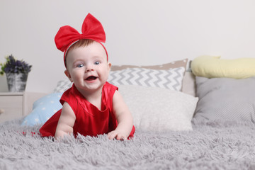 Cute funny baby in red dress and bow smiles on bed in bedroom