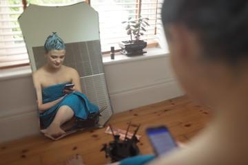 Woman using phone in bathroom