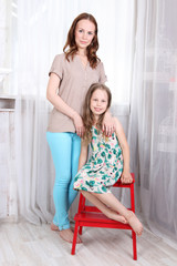 Happy girl with her mother pose on stool near window in light room