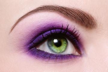 Macro shot of green woman's eye with violet eyeshadow, selective focus
