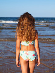 Braungebrannte junge Frau im Bikini schaut in Wellen am Meer