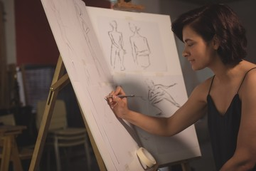 Female artist drawing a sketch on canvas