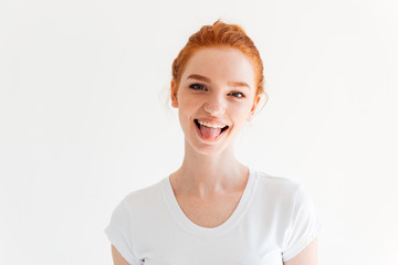 Happy ginger woman in t-shirt showing her tongue