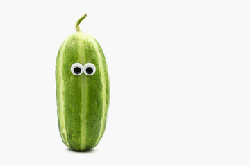 Crazy Carosello cucumber with googly eyes on white background, a variety of cucumber mixed with melon, cultivated in Apulia,