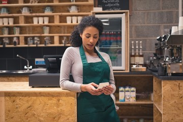 Beautiful waitress using mobile phone at counter