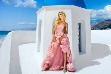 Beauties blonde young woman for long amazing white pink wedding sexy dress on the sea in Greece in Santorinii island