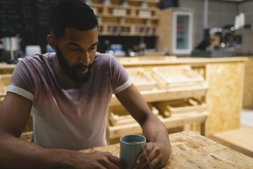 Thoughtful young man with coffee cup sitting at table