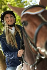 Closeup photo of blonde rider and horse
